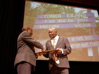 Van Troon (r) krijgt de award uitgereikt door André Pakosie
