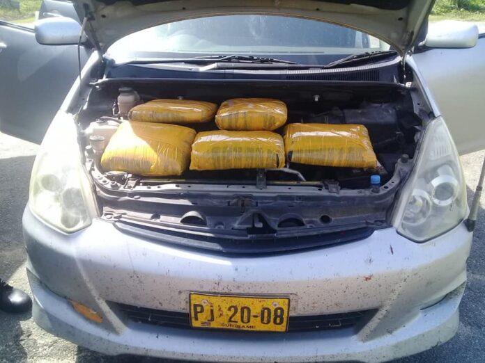 Taxi chauffeur verstopt pakken drugs bovenop de motor van zijn auto