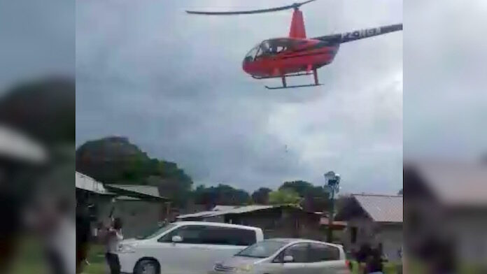 VIDEO: Helikopter strooit met geld in dorp Suriname?