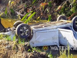 Auto over de kop in het water langs Oost-Westverbinding in Suriname