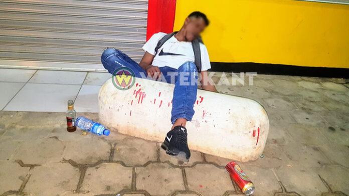 Dronken man slaapt roes uit voor gesloten winkel in Suriname