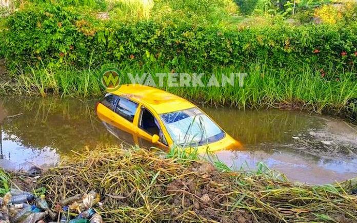 Taxichauffeur rijdt auto in de trens in Suriname