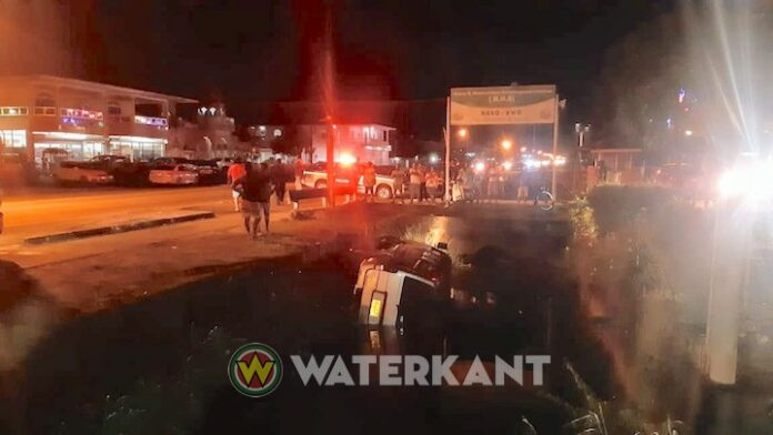 Auto in goot langs Indira Gandhiweg in Suriname
