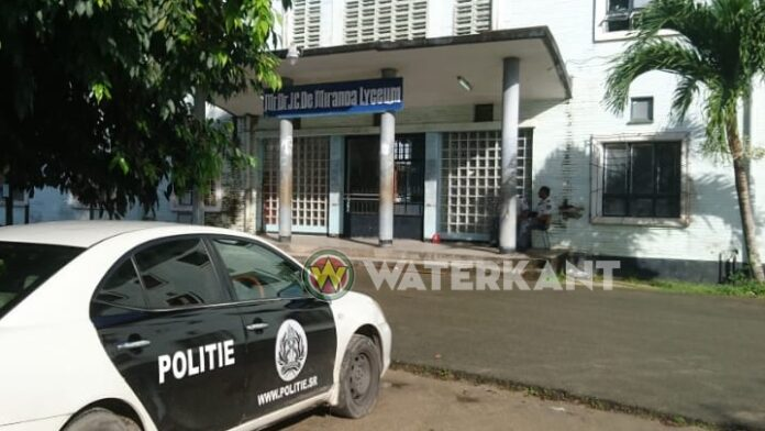 Een politieauto voor het gebouw van het Mr. Dr. J. C. de Miranda Lyceum (Lyco 1)