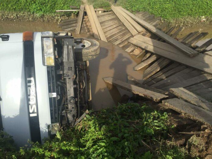 Truck valt in het water door kapotte brug in Suriname