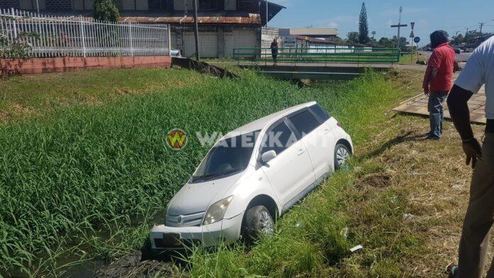 Auto in trens langs Indira Gandhiweg in Suriname