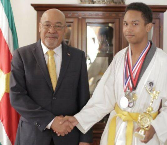 President Bouterse ontvangt 16-jarige winnaar gouden medaille