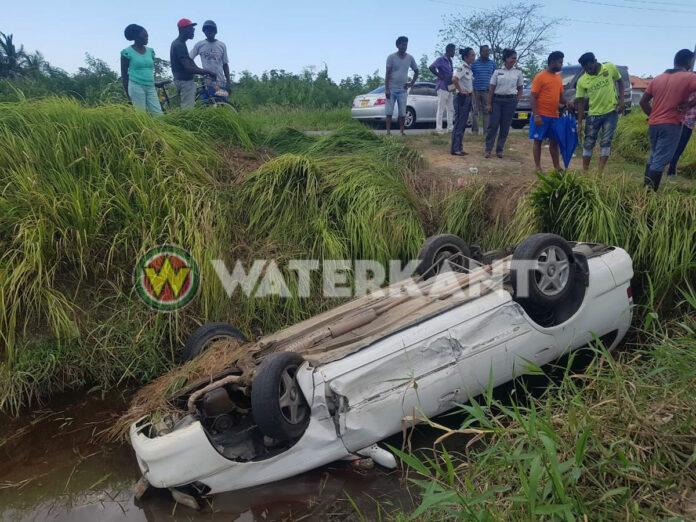 Auto op z'n kop in de goot na aanrijding in Suriname