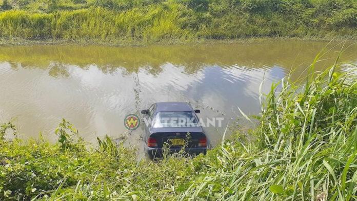 Auto eindigt in het water langs de weg in Suriname