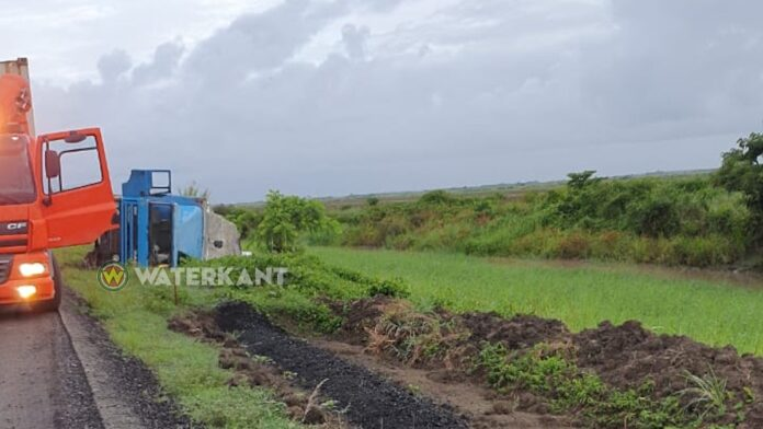 Truck met rijst op z'n zij in de berm langs de weg