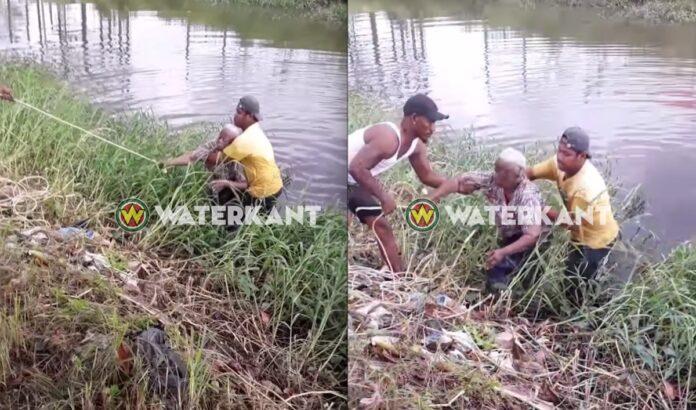 Mannen helpen oude vrouw die in kanaal viel