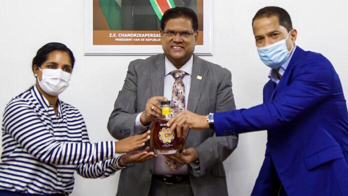 President Santokhi neemt eerste Borgoe Srefidensi Edition fles in ontvangst