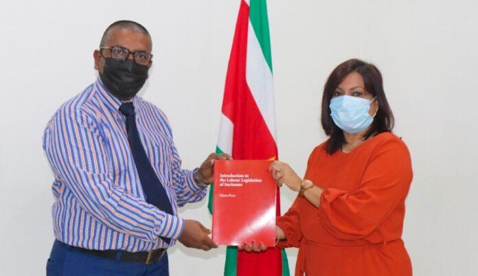 Minister Kuldipsingh neemt Engelstalig arbeidsboek in ontvangst