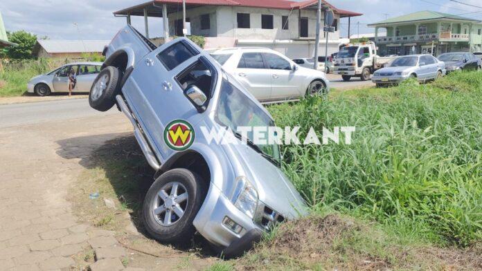 Pick-up zakt deels in goot na onoplettendheid bestuurder